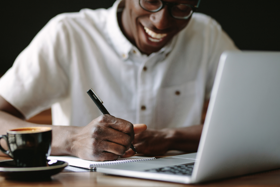 black man smiling and writing in notebook